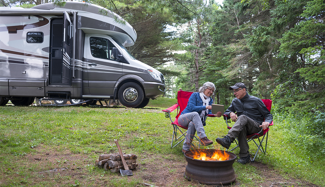 Couple looking at their tablet outdoors while camping