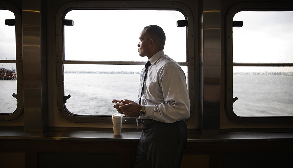 Businessman gazes out window of ferry building while using phone and having coffee