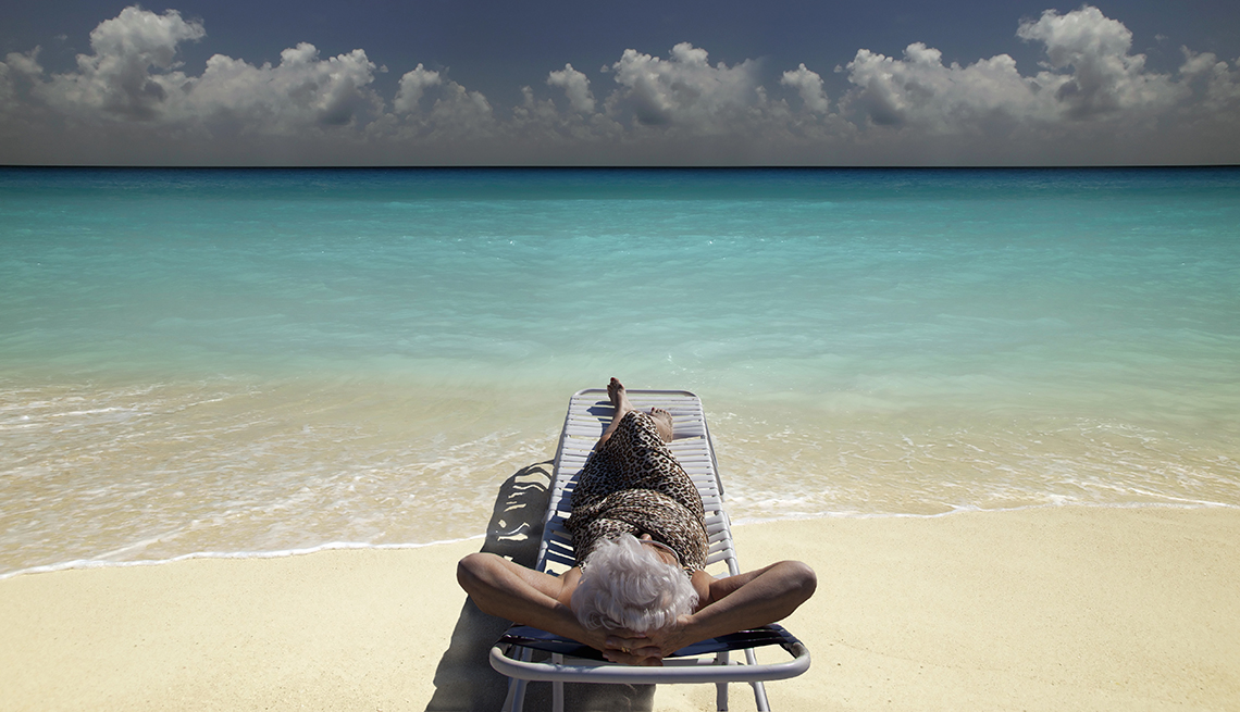 Mujer mayor recostada en una banca en la playa y mirando al cielo con el mar al fondo.