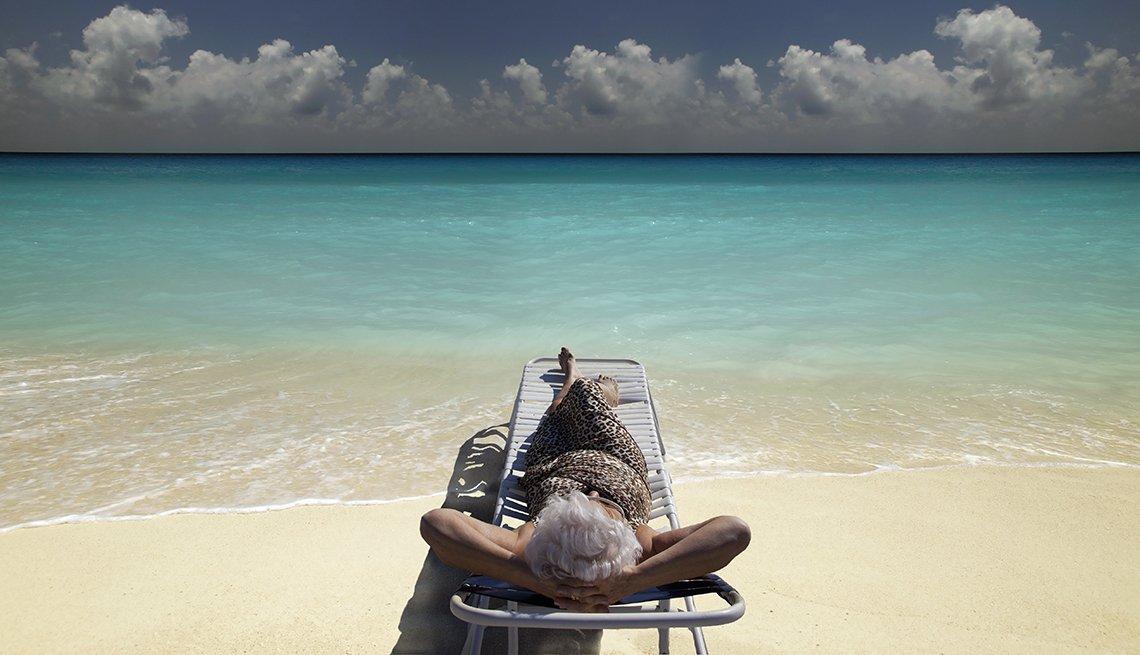 Senior Woman on beach lounger gazing at horizon