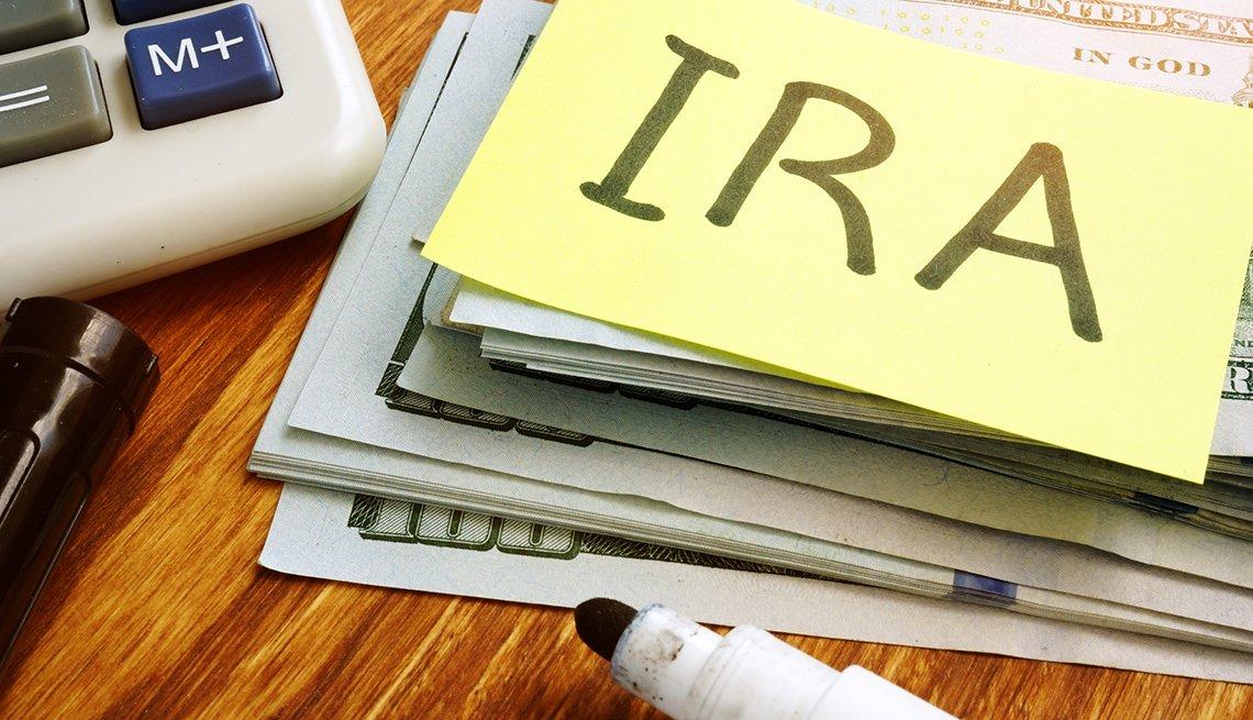 Papel con la palabra en inglés IRA, sobre varios dólares y una calculadora al lado.