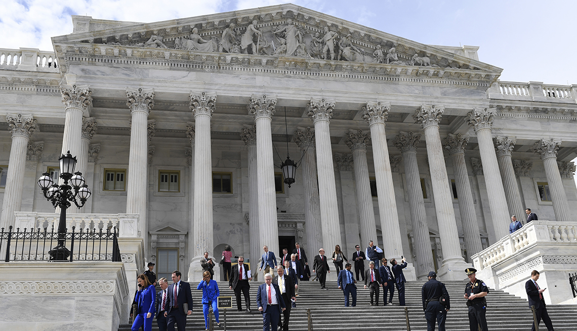 low angle of exterior of Capitol building with people in business suits walking down steps