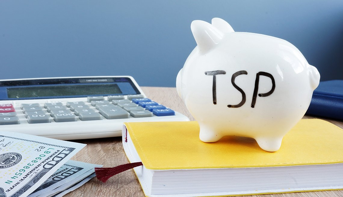 Thrift savings plan TSP written on a piggy bank on a desk with book, cash and calculator