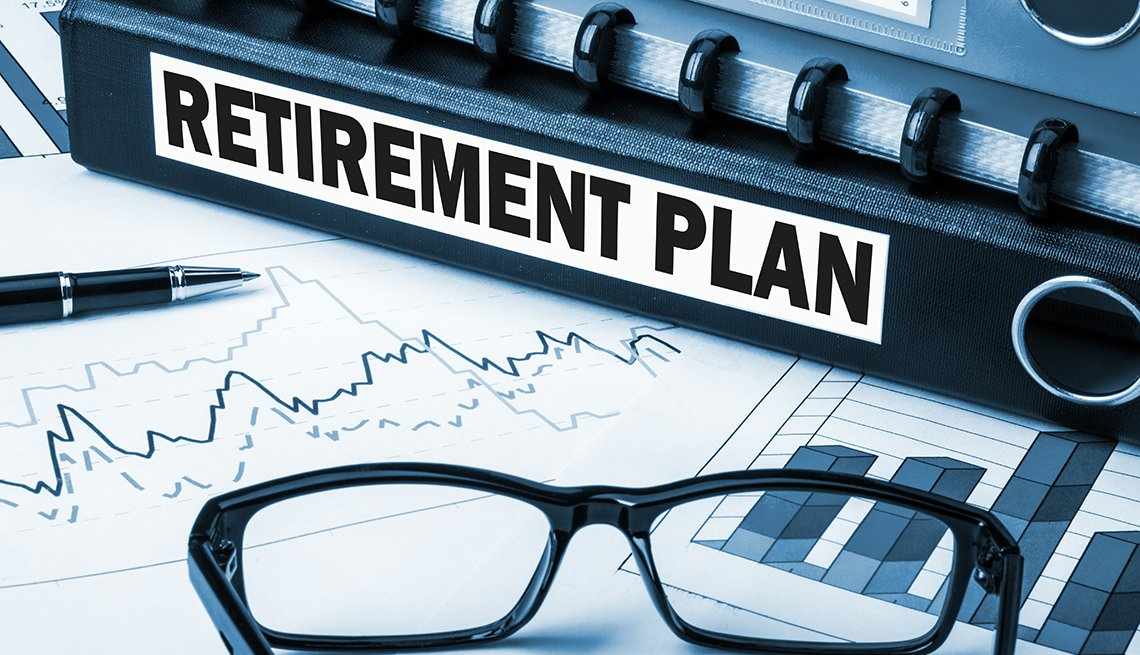 a binder spine label says retirement plan - it sits on graphs and glasses on desk