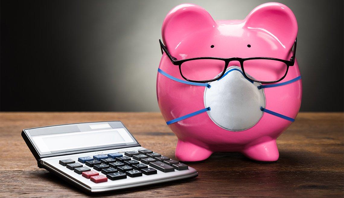 Alcancía de color rosado con gafas y tapabocas al lado de una calculadora.