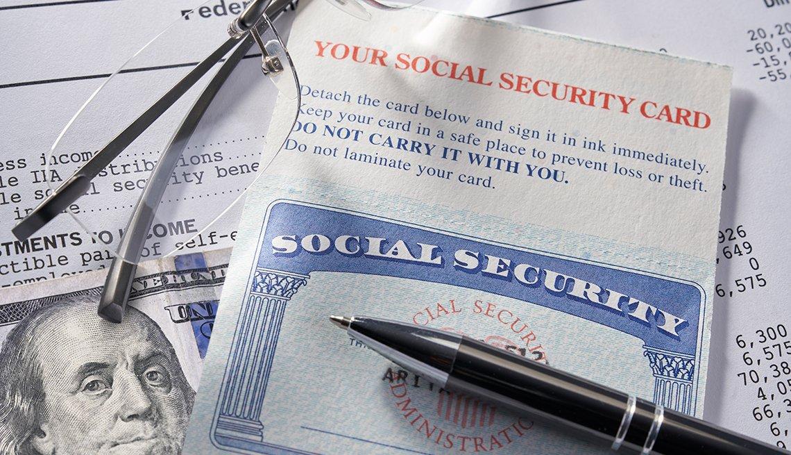 Tarjeta del Seguro Social sobre un billete de 100 dólares, unos lentes, un lapicero y un documento.