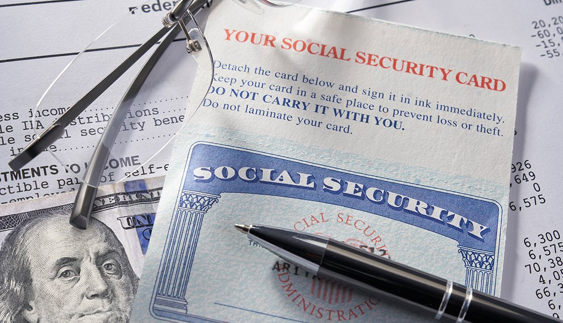 closeup display of Social Security card with money, pen, eyeglasses, $100 dollars