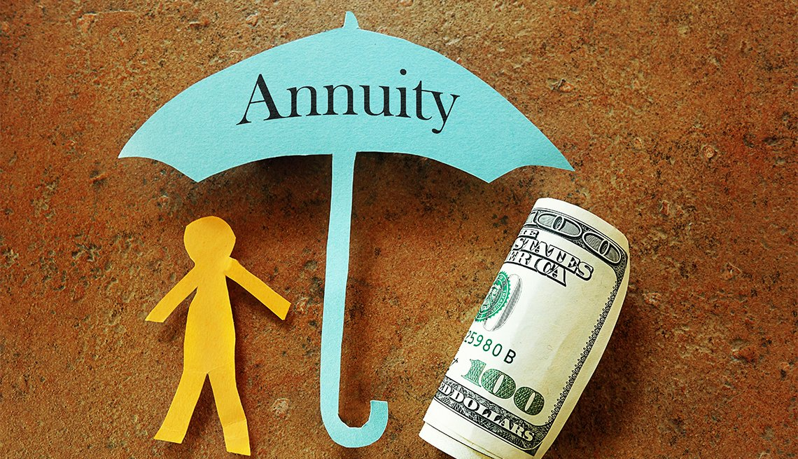 paper cut out stick figure and a rolled up hundred dollar bill sheltered under a paper cut umbrella labeled annuity