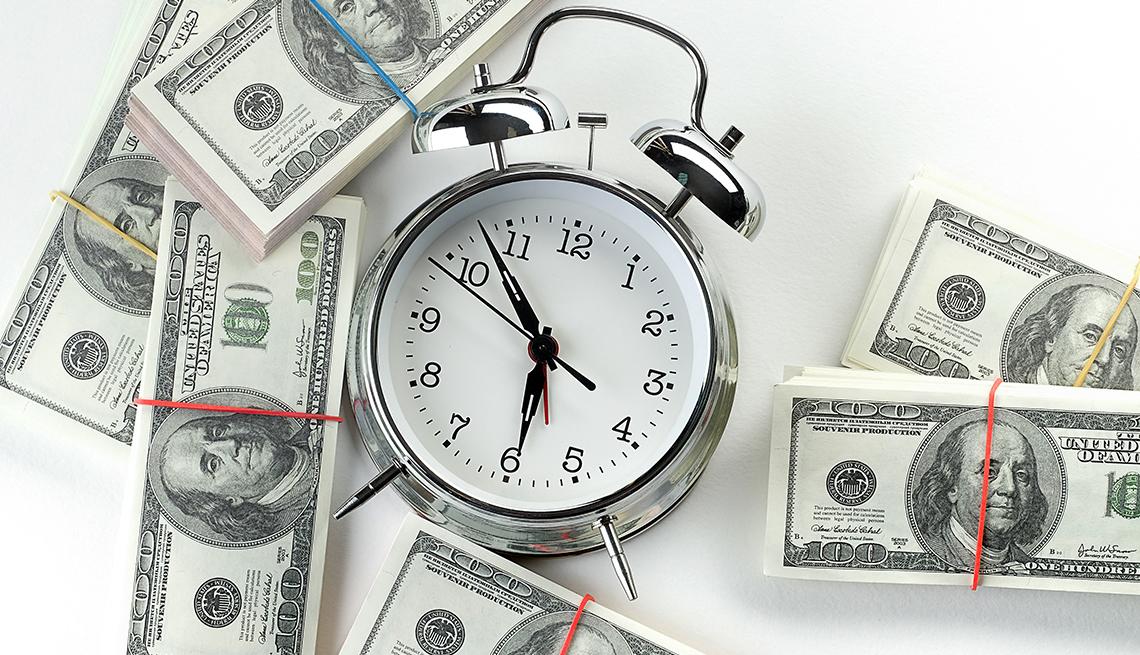 A shiny metal alarm clock surrounded by bundles of U.S. cash