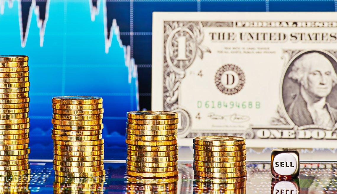Billete de dólar, monedas apiladas, y un cubo que dice vender, sobre una gráfica estadística.