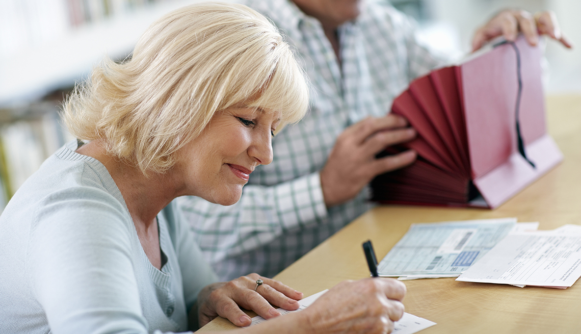 smiling woman in forground writing on financial document while in soft focus background a man is looking through a red accordian style home office file folder