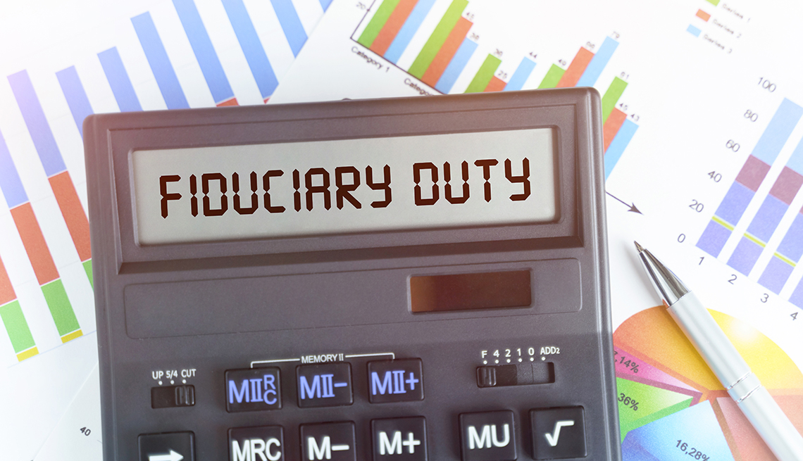 on a table are financial charts and a calculator that displays the words fiduciary duty
