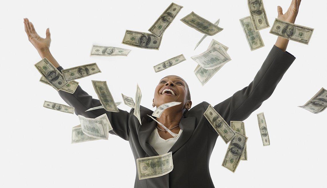 Mujer sonriendo, con los brazos abiertos y dólares cayendo sobre ella.