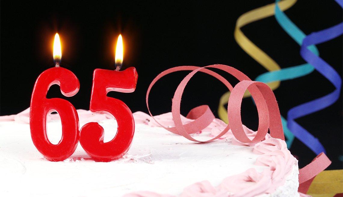 Pastel de cumpleaños con velas en forma de número 65.