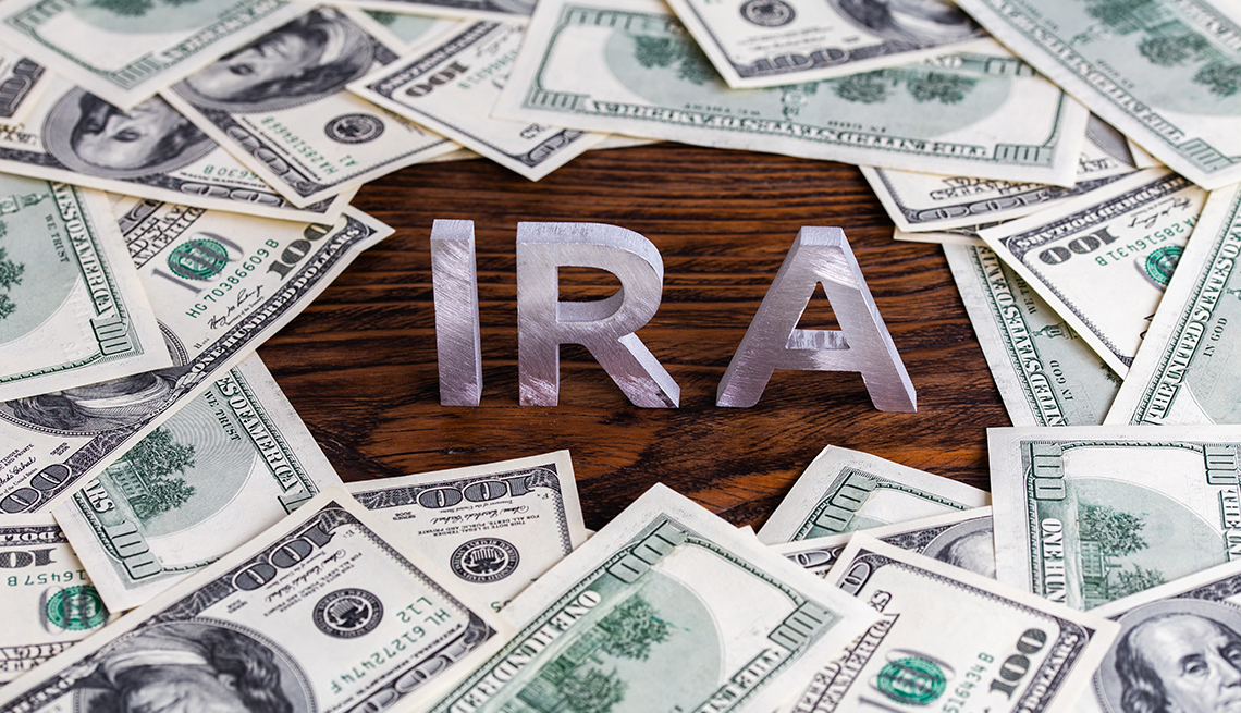 the word IRA made of silver metal letters on wooden background surrounded by one-hundred dollar bills
