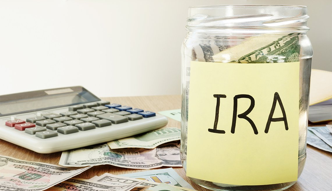 IRA escrito en una etiqueta pegada a un frasco con dólares.