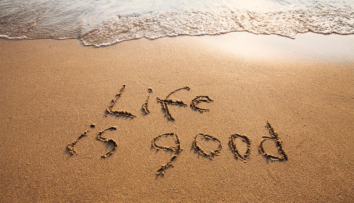 Palabras en inglés sobre la arena de una playa que dice la vida es buena.