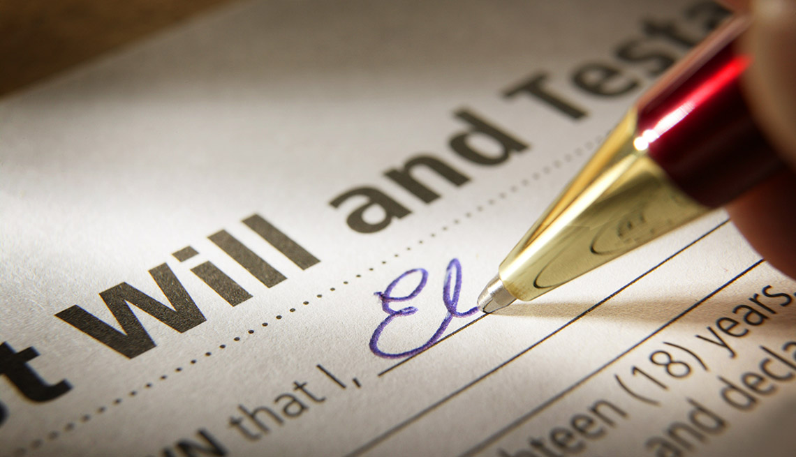 closeup of the signing of a last will and testament with a red and gold ballpoint pen writing in blue ink