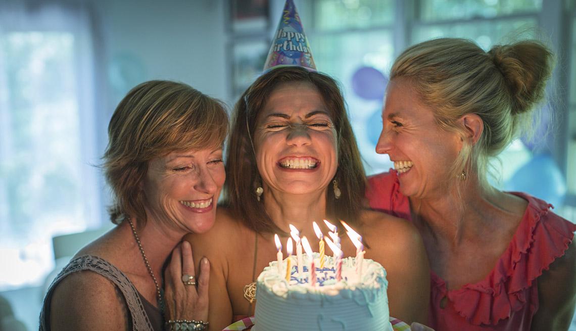 Mujer cierra los ojos, abre la boca y aprieta los dientes mientras sostiene un pastel con velas en medio de dos amigas