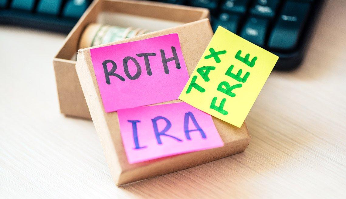 Papeles de notas que dicen ROTH IRA y libre de impuestos al lado de una caja con dólares enrollados.