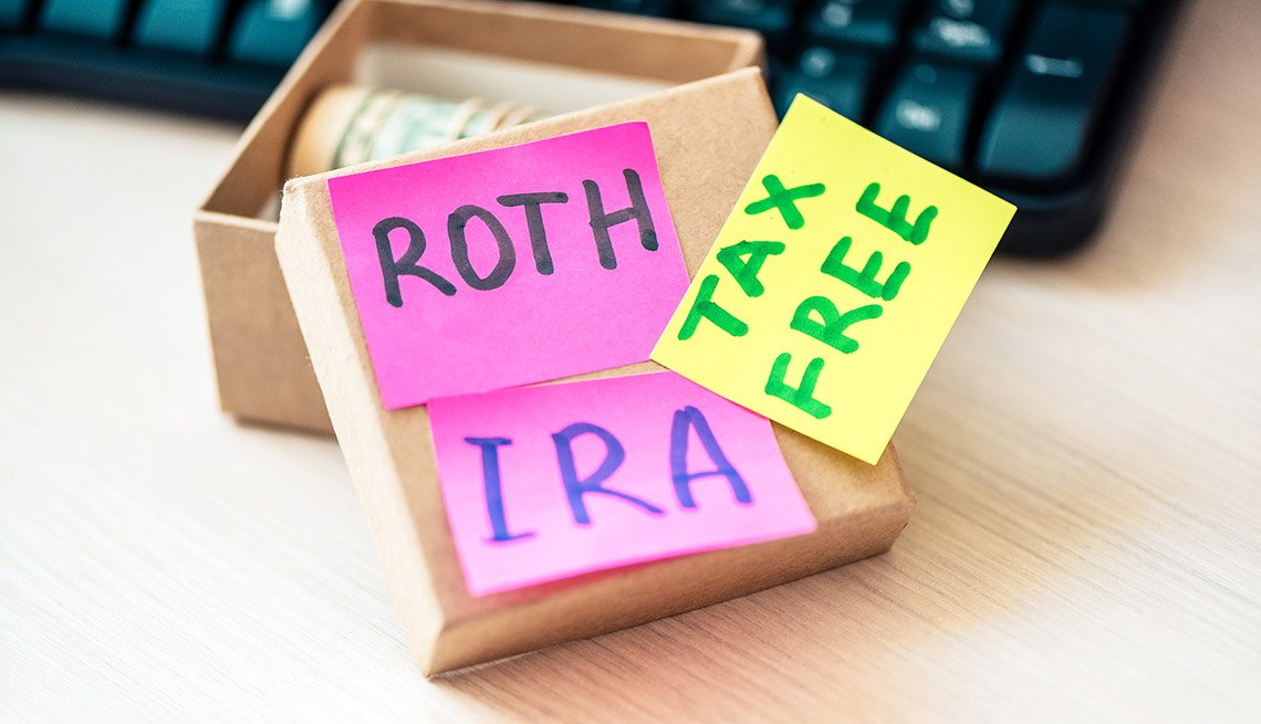 """the words """"ira roth tax free"""" are written on pink and yellow post-it notes stuck on the lid of a box of money"""