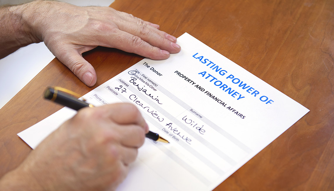 close up of hands writing on a power of attorney form for property and financial affairs
