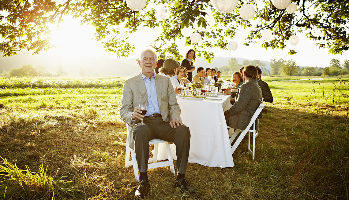 Senior man holding glass of wine sitting at head of banquet table outside in field friends and family seated behind
