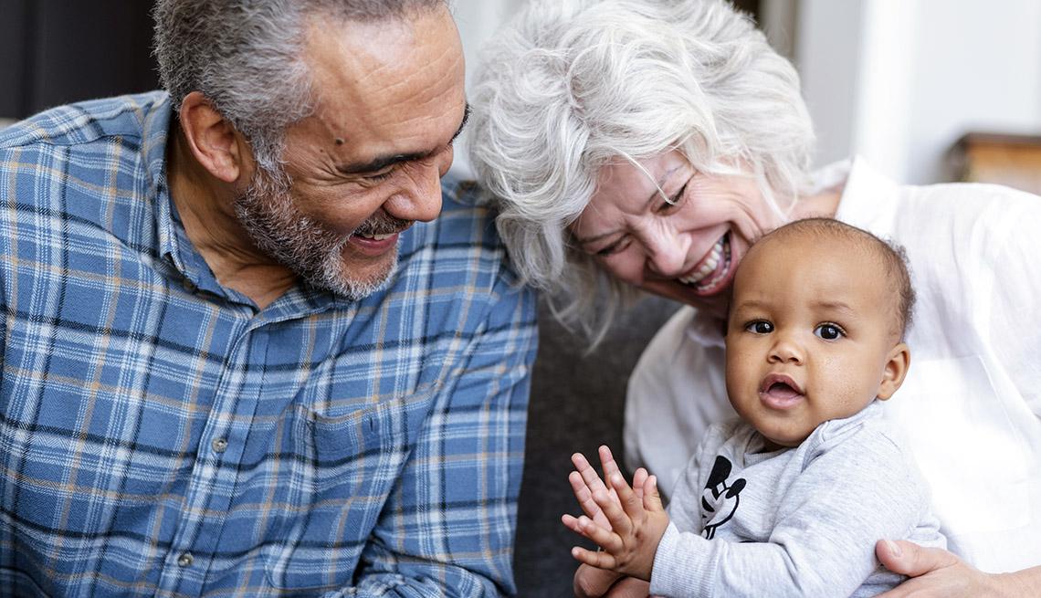 Abuelos sentados en un sofá sosteniendo a su nieto