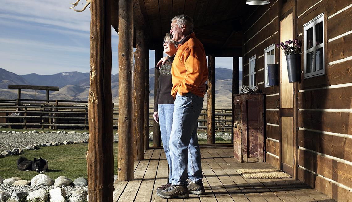 Pareja mira el paisaje desde la entrada de una cabaña en las montañas