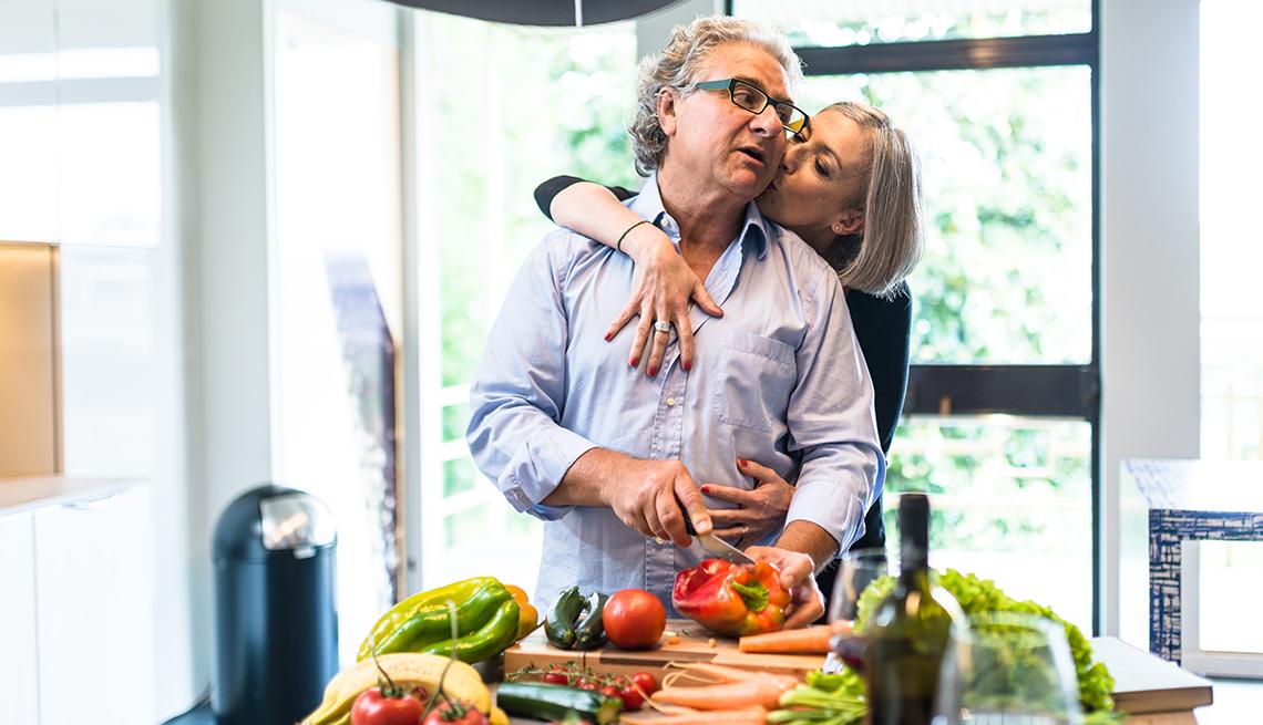 Hombre cocinando en su casa mientras su esposa lo abraza por detrás y le da un beso.