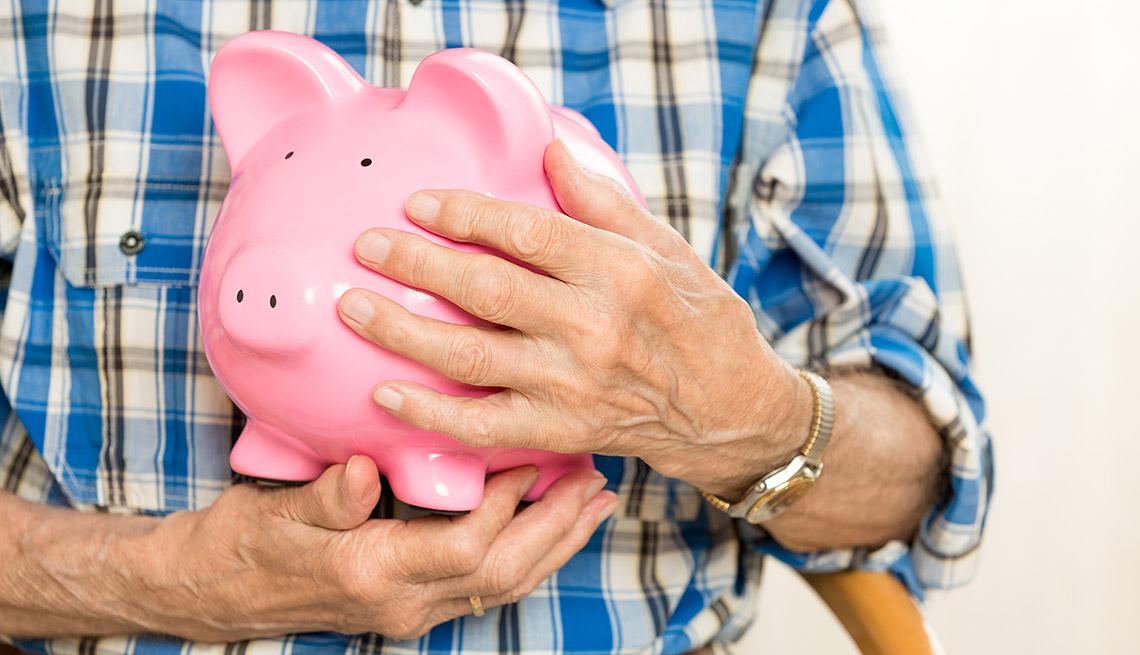 Persona mayor sosteniendo una alcancía en forma de chochinito rosado