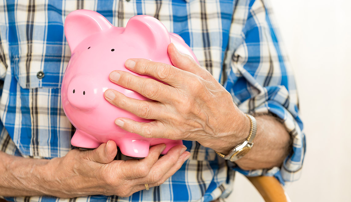 close up of hands holding a piggy bank protectively close to the chest
