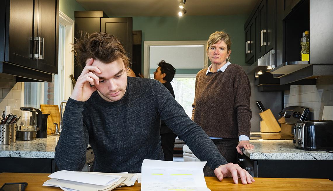 Mujer mayor viendo a su hijo chequeando facturas y deudas sobre una mesa en la cocina.