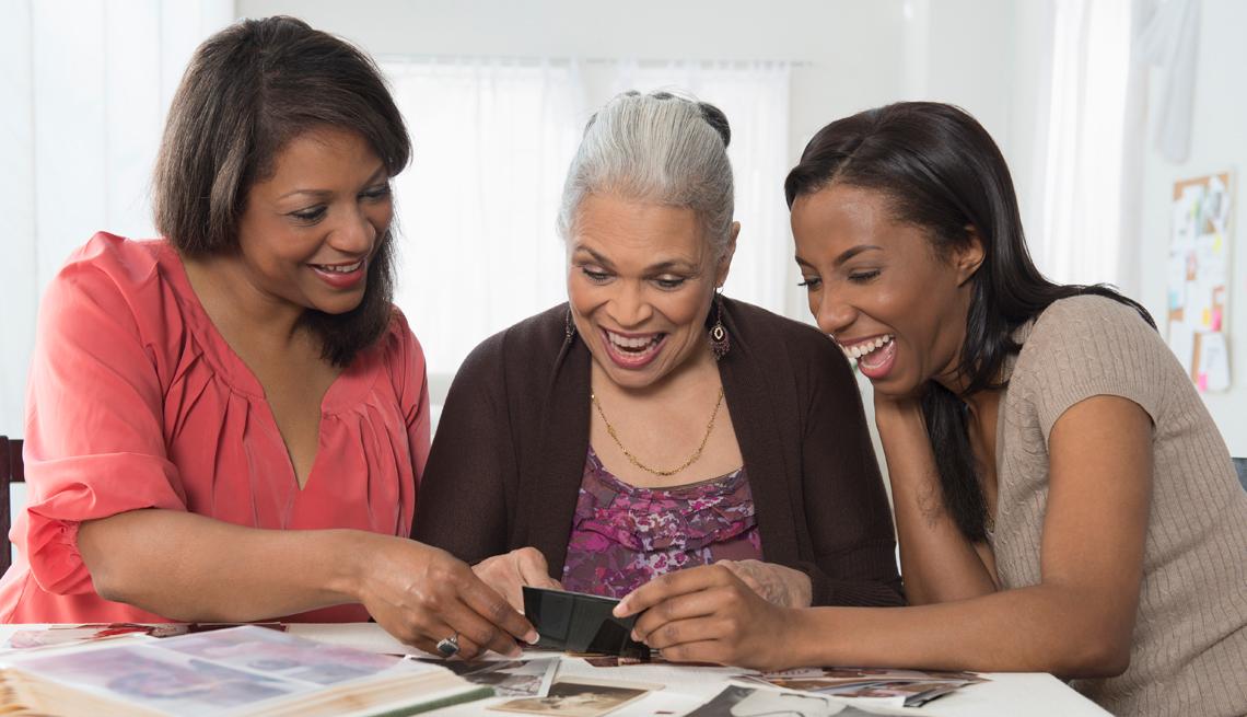 Tres generaciones de mujeres viendo fotos