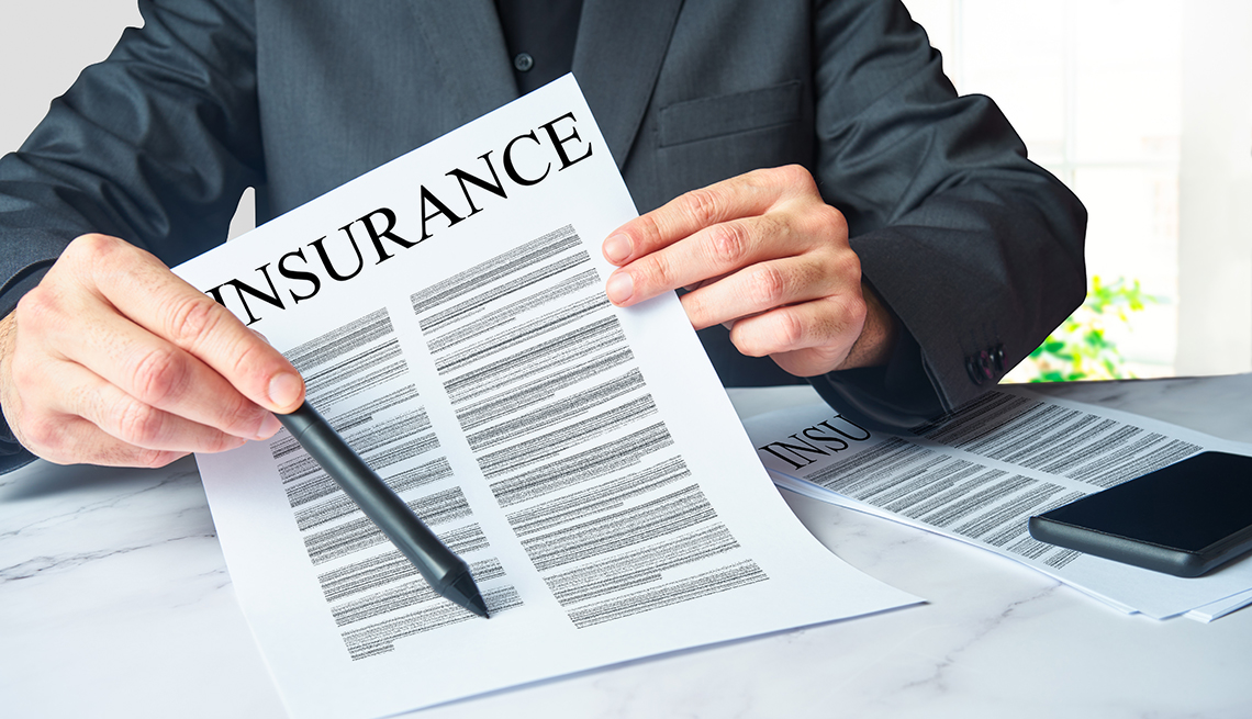 An insurance agent is presenting a policy contract  for an unseen clientto sign