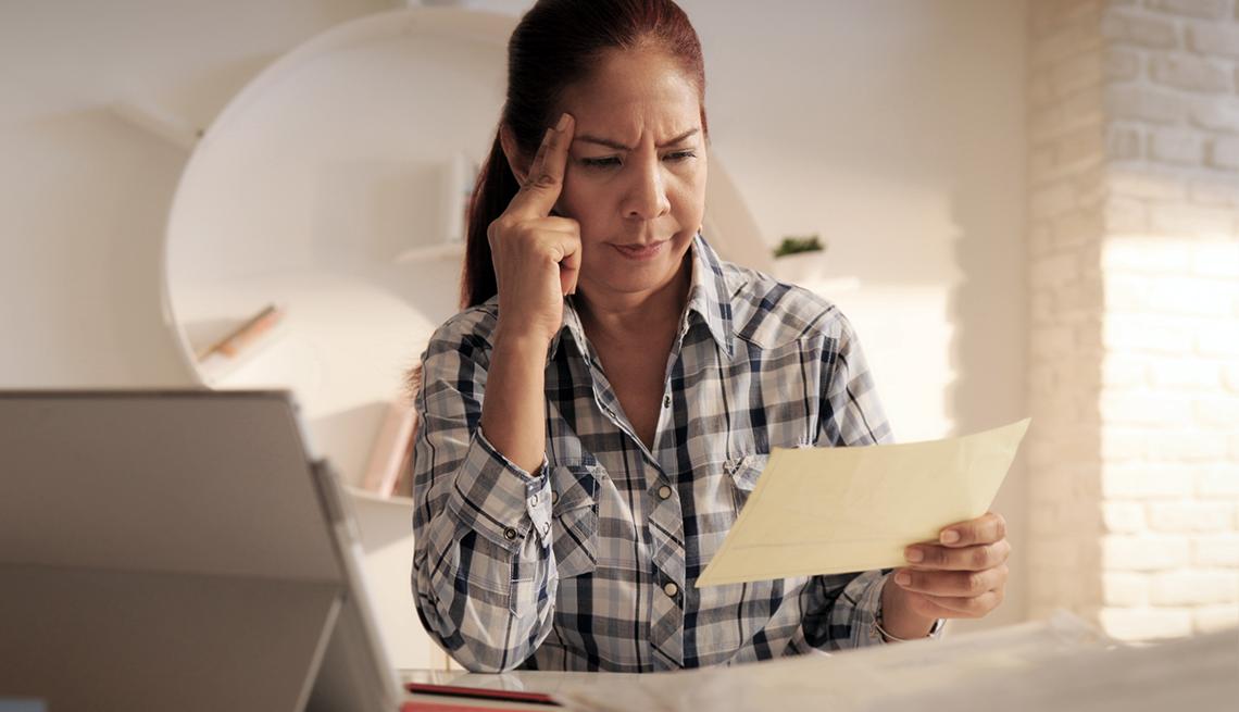 Mujer mira un documento mientras coloca el dedo índice en su cabeza para fijar su mirada. Al lado tiene una computadora.