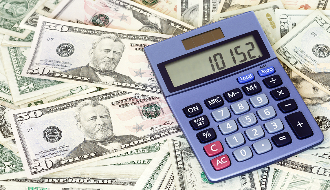 A blue calculator sits on a background of U.S. currency of varying dollar amounts.