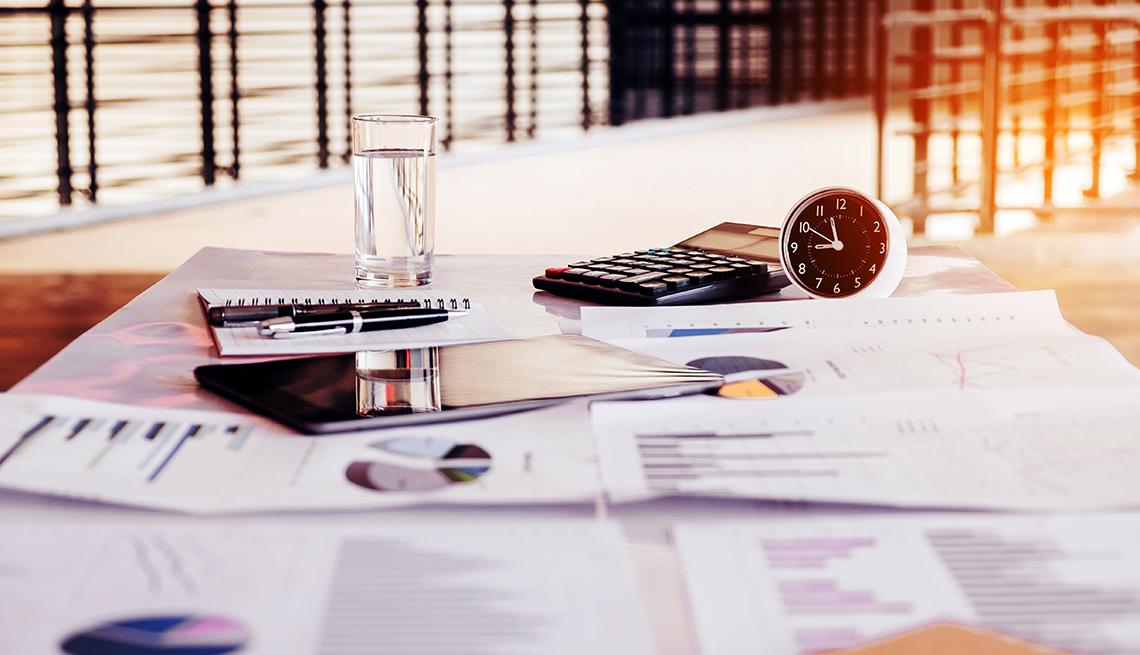 Escritorio con documentos financieros, una tableta, un reloj, un vaso, una calculadora