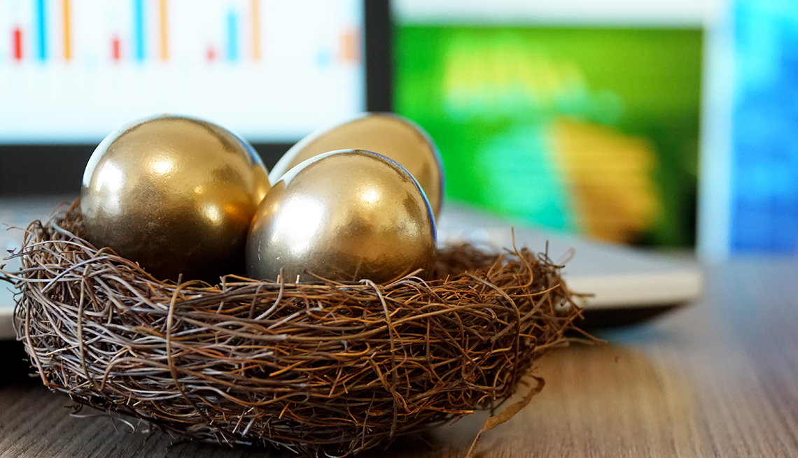 a basket of golden nest eggs in front of soft focus investment screens on computers