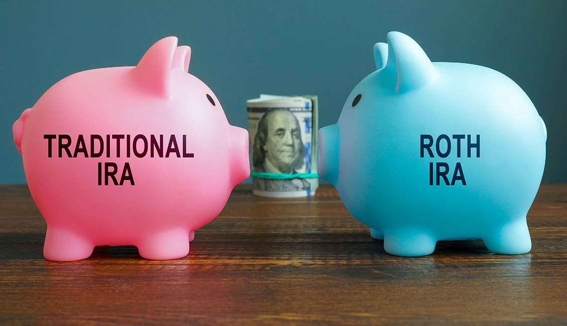 """face-off between a pink piggy bank labeled """"Traditional IRA"""" and a blue piggy bank labeled """"Roth IRA"""" with  a roll of money behind them"""