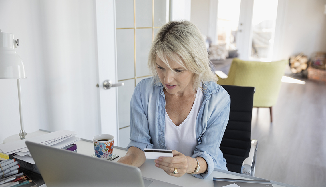 Woman paying bills with credit card at laptop in home office