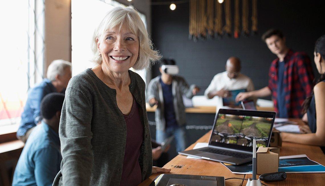 Mujer mayor en un escritorio y con una computadora al lado