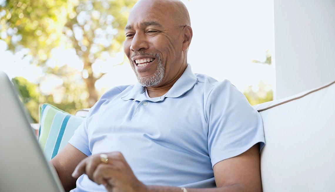 Hombre sentado y con una computadora personal en las piernas