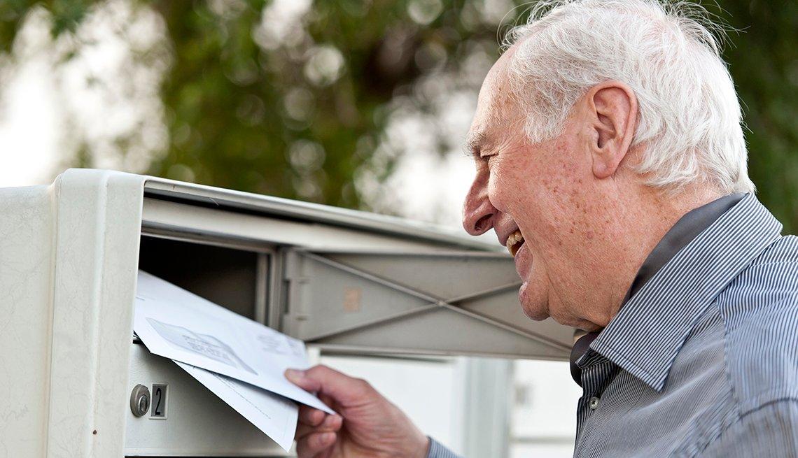 Señor mayor colocando unos sobres en el buzón del correo.