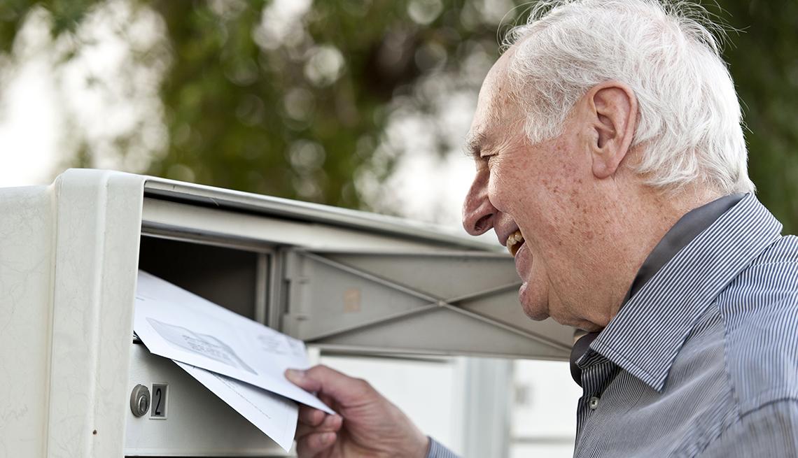 item 1 of Gallery image - Señor mayor colocando unos sobres en el buzón del correo.