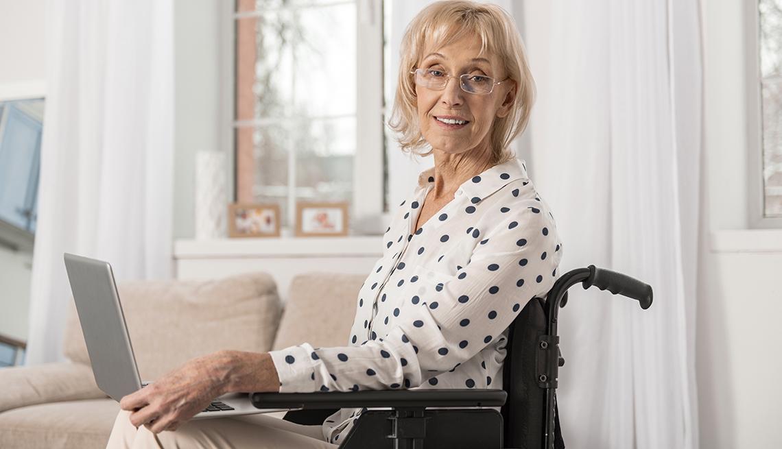 item 5 of Gallery image - Mujer mayor en una silla de ruedas y con una computadora en la mano