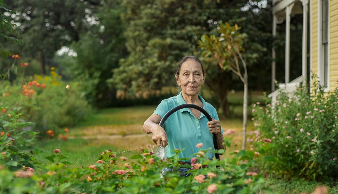 item 4 of Gallery image - Cenorina Olivares tending to her garden