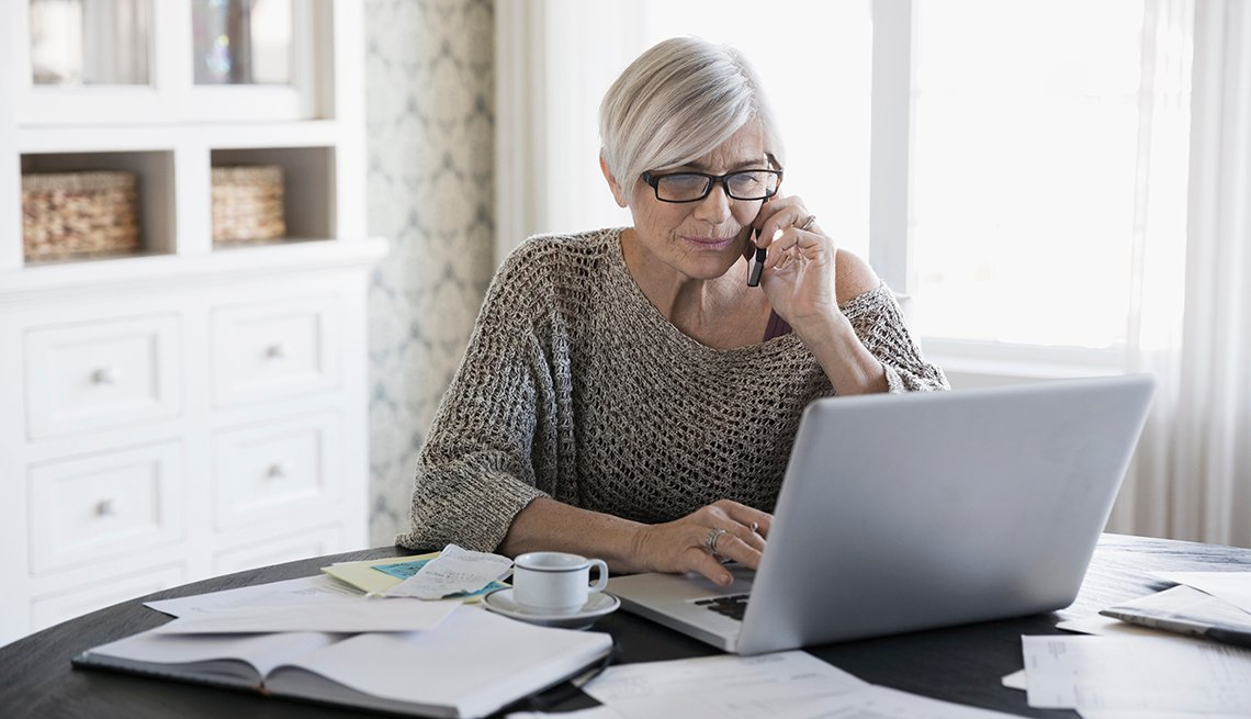 mature woman on the phone while sitting at a table with a bunch of paperwork