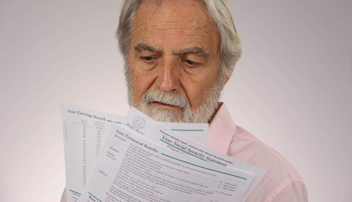 Hombre sosteniendo informes del Seguro Social
