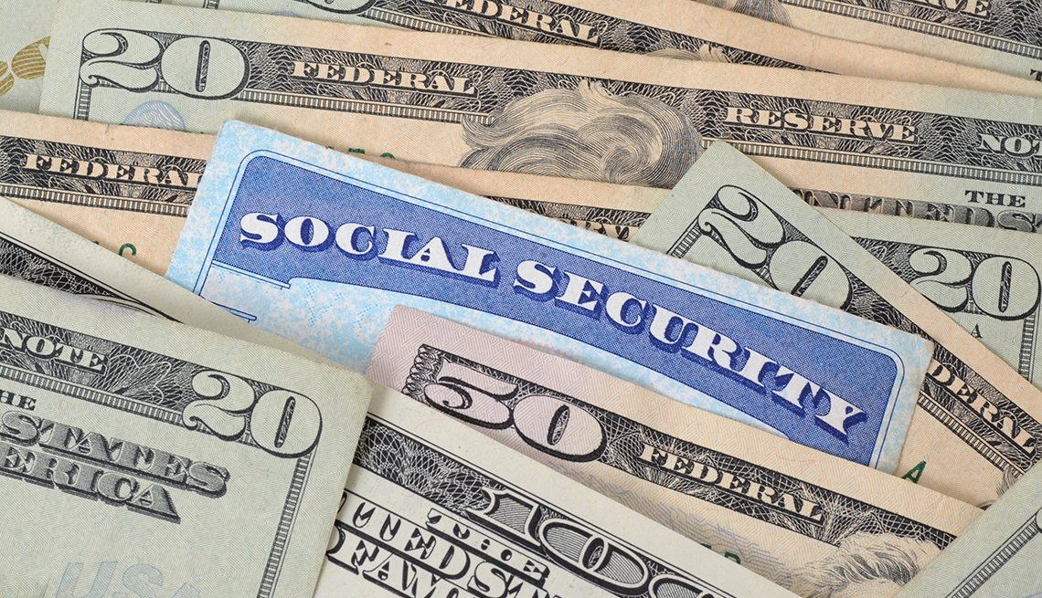 Tarjeta del Seguro Social en medio de billetes de $20 dólares.